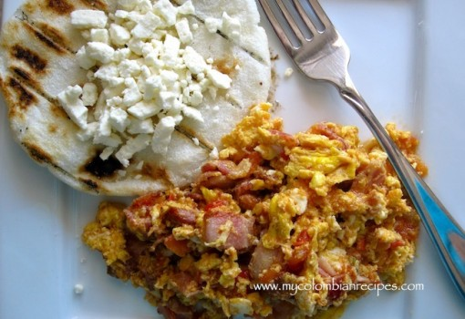 "<span class=""p-name"">Huevos Pericos con Tocineta (Scrambled Eggs with Tomatoes, Scallions and Bacon)</span>"